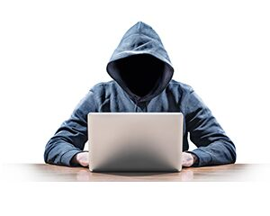 Suspicious person sitting in front of a laptop