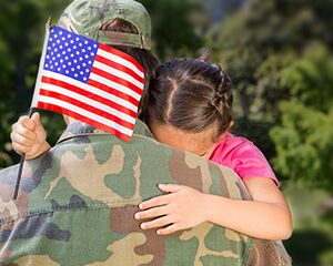 Girl hugging military parent