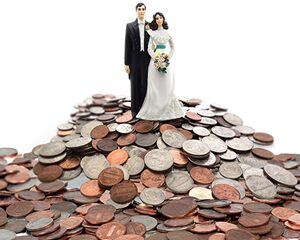 wedding cake topper sitting on top of a large stack of coins