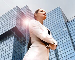 businesswoman standing in front of tall building