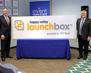 Jim Hoehn and Eric Barron unveil the new Happy Valley LaunchBox Powered by PNC Bank logo