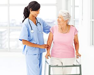 nurse assisting elderly woman with a walker
