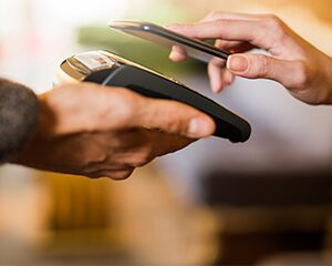 closeup of one hand holding a payment terminal and another hand holding a mobile phone to make a payment