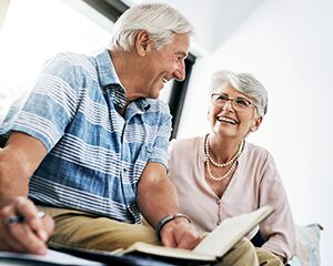 older man and woman holding a notebook and a pen while talking to each other