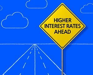 "yellow road sign that says ""higher interest rates ahead"""