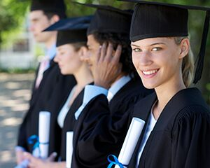 students smiling in caps and gowns