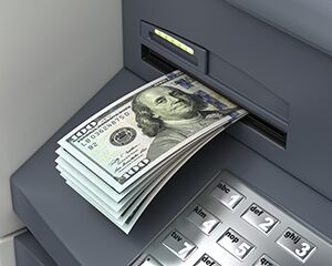 Stack of hundred dollar bills coming out of ATM