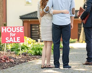 "couple standing in front of a ""house for sale"" sign"