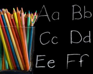 container of colored pencils with blackboard and letters