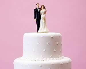 wedding cake with bride and groom topper, pink background