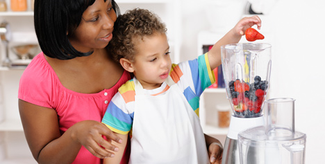 adult with child filling a blender with fruit